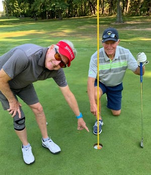 Playing partner Jim Earnshaw points to the hole-in-one by Gary Smith while competing last Saturday in the Shelby Golf Course Ryder Cup