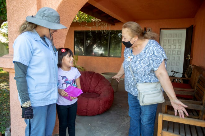 Yuidth Ortega, a second-grader at Sunny Sands Elementary School, receives a prize for an attendance drawing from Palm Springs Unified School District Community Liaison Lilian Torres, right, as her mom Yesenia Lemus looks on at their home in Cathedral City, Calif., on September 16, 2020. Ortega has been attending online classes every day amid the ongoing pandemic-induced closure of schools.