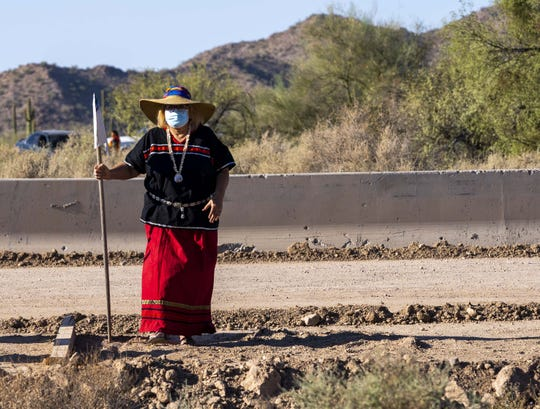 Eleanor Ortega, walks towards the runner at the border wall during a ritual ceremony by Tohono and Hia-Ced O'odham organized a cross-border prayer run and ceremony to reaffirm religious and cultural practices along the Arizona-Mexico border. For tribal nations along the U.S.-Mexico border, such as the Hia-Ced and Tohono O'odham, the construction of these border barriers threatens to further sever their members living on the Mexican side from the tribal communities, rituals and services in the United States.