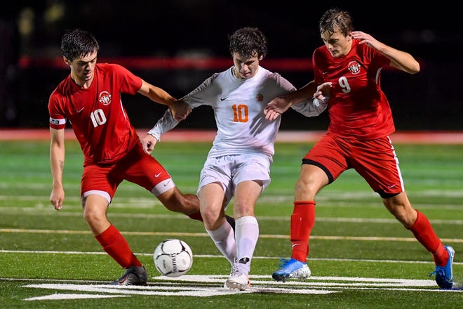 York Suburban's Paker Lando, center, battles for control of the ball with Nick Holloway, left, and Mason Kaifer of Susquehannock, Tuesday, September 29, 2020.