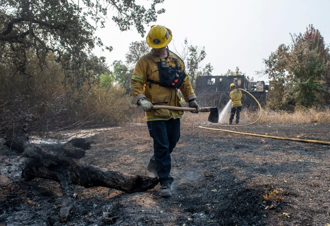 Chris Shussler, San Bernardino County firefighter puts out a hotspot with his fellow firefighter in the Skyhawk neighborhood in Santa Rosa, Calif., on Tuesday, Sept. 29, 2020.