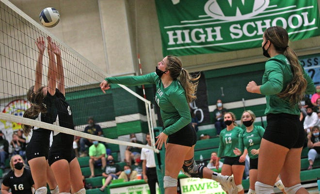 Kaitlyn Stephens, center, spikes the ball for Wall during a game against Grape Creek on Tuesday, Sept. 29, 2020.