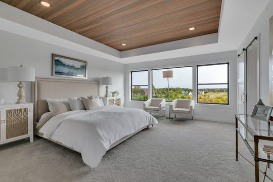 The master bedroom offers a ship lap cedar ceiling, a barn door and glorious views of the landscape.