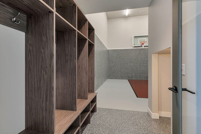 The sport court area on the lower level features a built-in shelving system, under step storage and a custom floor.