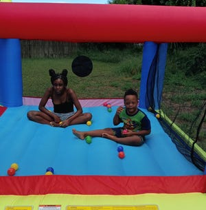 Raymond Brannon, right, and sister Tyeishai Woodard, both of Vero Beach, enjoy the bounce house gifted to Raymond through the Sunshine Foundation. The nonprofit grants the wishes of children with life-long chronic illnesses.