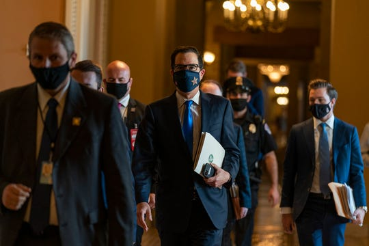 Treasury Secretary Steven Mnuchin, walks from the office of Senate Majority Leader Sen. Mitch McConnell of Ky., as he leaves the Capitol, Wednesday, Sept. 30, 2020, in Washington.