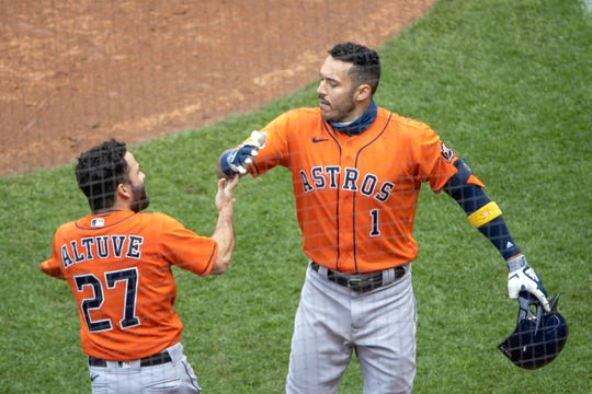 Carlos Correa celebrates his seventh-inning home run with Jose Altuve.