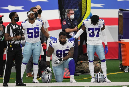 Dallas Cowboys defensive tackle Dontari Poe (95) kneels during the national anthem prior to the game against the Atlanta Falcons at AT&T Stadium.