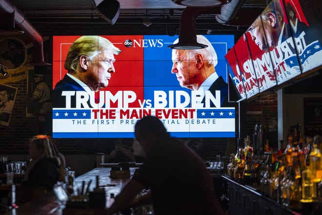Television screens airing the first presidential debate are seen at Walters Sports Bar in Washington.