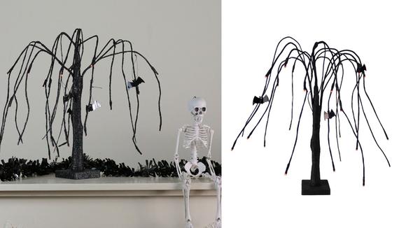 A spooky scary skeleton next to a spooky scary tree.