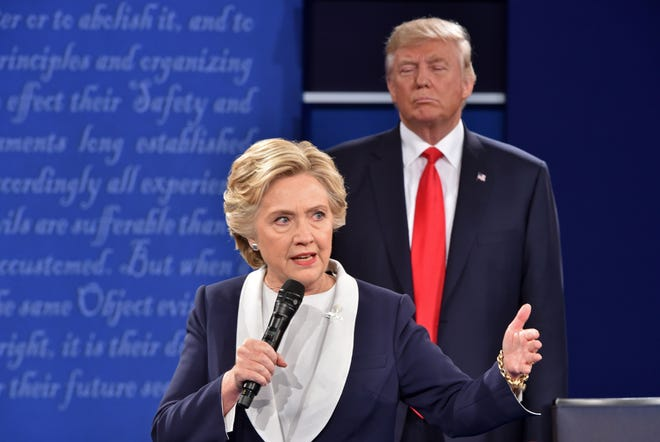 Then Republican presidential candidate Donald Trump listens to then Democratic presidential candidate Hillary Clinton during the second presidential debate at Washington University in St. Louis, Missouri, on Oct. 9, 2016.