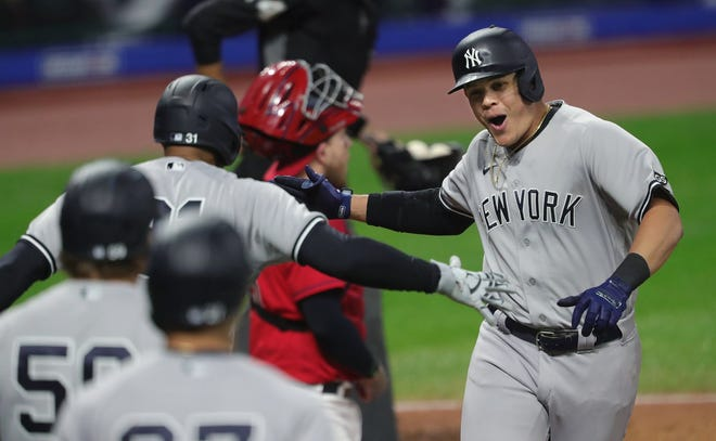 New York Yankees third baseman Gio Urshela, facing, celebrates at home plate with teammates after hitting a grand slam during the fourth inning of Game 2 of the American League Wild Card Series against the Cleveland Indians, Wednesday, Sept. 30, 2020, in Cleveland, Ohio. [Jeff Lange/Beacon Journal]