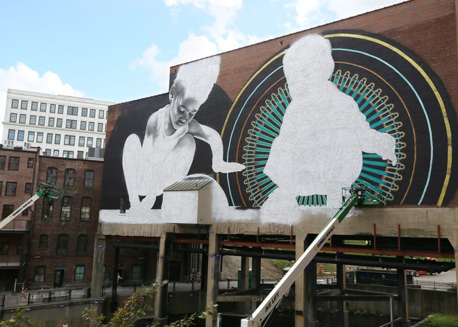 Muralist Aiseborn of Los Angeles works on a mural created by Aiseborn and El Mac on the exterior of the Akron Civic Theatre on Thursday.