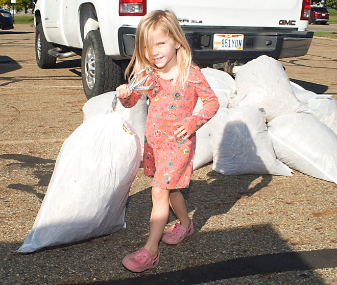 Bellamy Ellington, 4, carries a bag of straw that will be used to create a scarecrow for the upcoming Louisville Area Chamber of Commerce's Scarecrows on Parade event. Materials pickup took place Sept. 25-26.