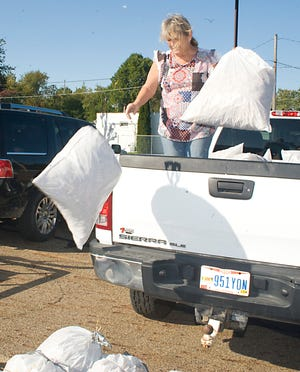 Becky Thompson tosses bags of straw from a pickup truck Sept. 26 for the upcoming Louisville Scarecrows on Parade event. Participants have two weeks to create their scarecrows before the judging event on Oct. 10.