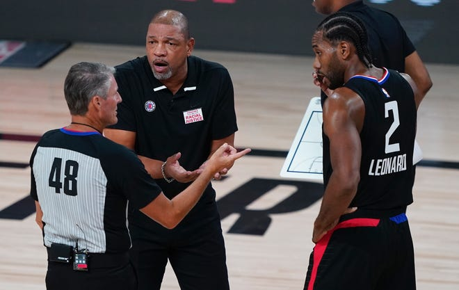 Clippers coach Doc Rivers makes his point to referee Scott Foster as Los Angeles' Kawhi Leonard listens.