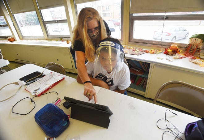 """Volunteer Kathleen """"Kitty"""" Curtis of Economy helps third-grader Jaysean Tarpley connect to a class on his iPad. Jaysean, 8, is among 20 pupils in the Ambridge Area School District engaged in virtual learning at Safe Haven Learning Pod at Good Samaritan Catholic Church in Ambridge. The parish created a safe spot for elementary pupils to do their schoolwork when remote learning and parents aren't home to supervise."""