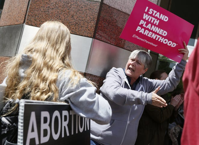 Mary Dillon, a pro choice protester, argues with anti-abortion protester Evangeline Dunn of Columbus at A Stop The Bans protest at the Riffe Center in May 2019. [Eric Albrecht/Dispatch]