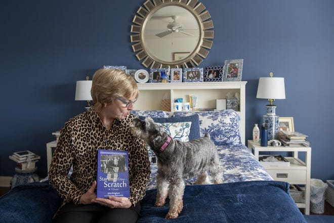 Cheryl Achterberg blows kisses to her miniature schnauzer, Rebel, in her Upper Arlington apartment, while holding a copy of a memoir written by her 86-year-old husband, John Brighton. He suffers from dementia and lives in a Powell memory care facility, which Achterberg is rarely able to visit because of concerns about transmitting COVID-19.