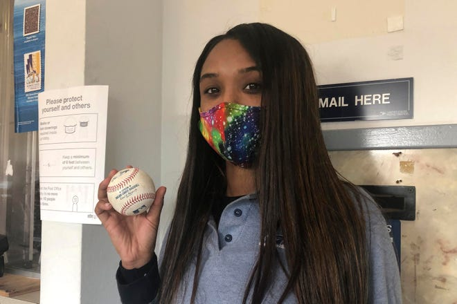 U.S. Postal Service worker Tionne Eitz holds a foul ball gift in Alameda, Calif.