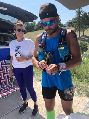 Nic Chiri takes a brief break during the Booneville Backroads Ultra-Marathon last month in Booneville, Iowa as his aunt Gina Chiri looks on.