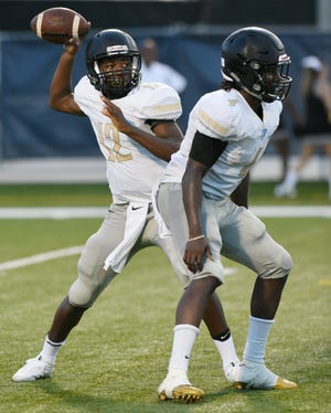 Oakleaf quarterback Walter Simmons III (left) drops back to pass against Camden County in his high school debut on Aug. 18, 2017. Simmons, now a senior committed to East Carolina, faces the Knights for their final meeting Friday.