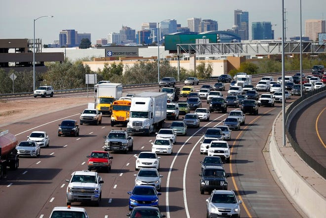In this Jan. 24, 2020, file photo, early rush hour traffic rolls along I-10 in Phoenix. Traffic deaths in the U.S. fell for the third straight year in 2019, the government's road safety agency said Thursday, Oct. 1.  The National Highway Traffic Safety Administration says the downward trend is continuing into this year with people driving fewer miles due to the pandemic.