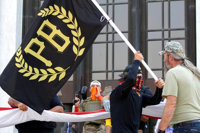 """In this Sept. 7, 2020, photo, a protester carries a Proud Boys banner, symbol of a right-wing group, while other members start to unfurl a large U.S. flag in front of the Oregon State Capitol in Salem, Ore. President Donald Trump didn't condemn white supremacist groups and their role in violence in some American cities this summer. Instead, he said the violence is a """"left-wing"""" problem and he told one far-right extremist group to """"stand back and stand by."""" His comments Tuesday night were in response to debate moderator Chris Wallace asking if he would condemn white supremacists and militia groups. Trump's exchange with Democrat Joe Biden left the extremist group Proud Boys celebrating what some of its members saw as tacit approval."""
