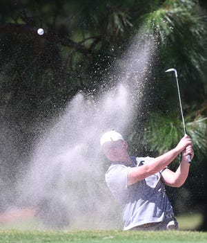 Justin Burroughs, Pensacola Catholic, blasts out from a green side bunker during the boys Miracle Strip Invitational Golf Tournament at Fort Walton Beach Golf Club Thursday.