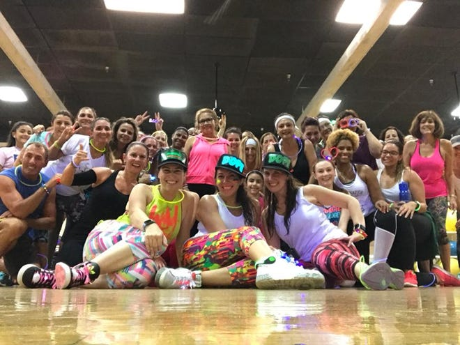 Jamie Tizol (front row, center) poses with her students after a themed Zumba class at the Wellington Community Center.