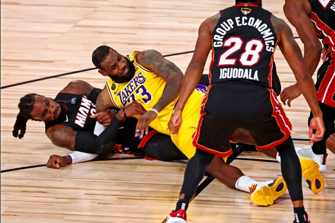 The Lakers' LeBron James (23) and Heat forward Jae Crowder fight for the ball on the floor during the second quarter of Wednesday night's NBA Finals Game 1 in Lake Buena Vista.