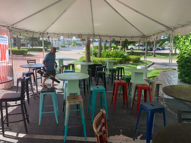 Tables and stools are set up under a tent outside Double Roads Tavern in Jupiter.