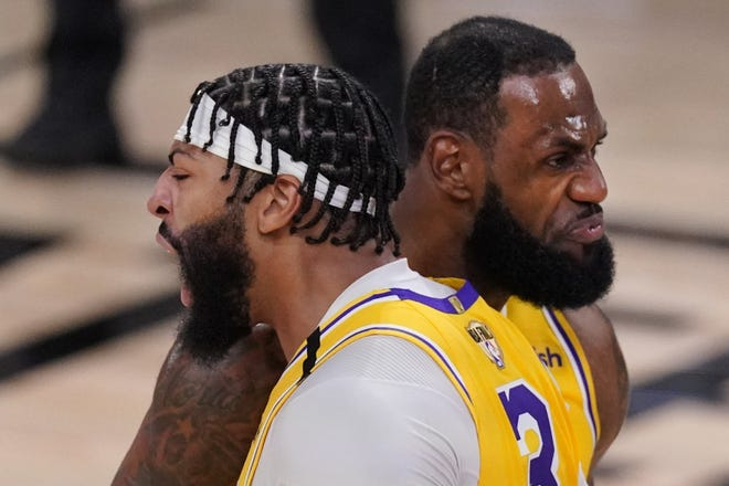 Lakers stars Anthony Davis, left, and LeBron James bump shoulders while celebrating a dunk against the Heat during the second half Wednesday night in Lake Buena Vista.