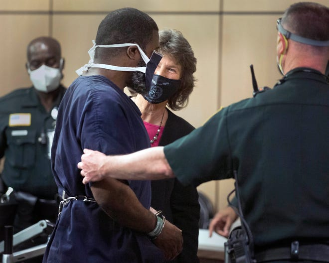 Public Defender Carey Haughwout smiles at Kevin Nelms as he is led from court after his resentencing hearing Thursday in West Palm Beach. Circuit Judge Charles Burton lowered the life sentence he received in 1984 as a 16-year-old. He could be out of prison soon.