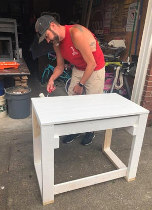 Alex Stanford paints a school desk that he built for a neighbor's child for her in-home virtual learning space on Sept. 15, 2020.