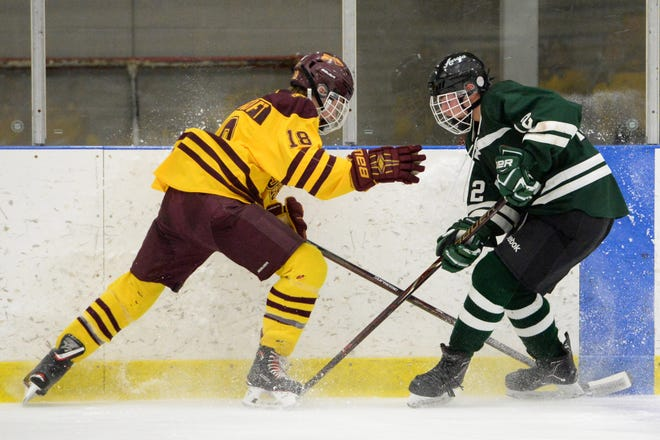 Walsh Jesuit's Charlie Huscroft (18) fights for the puck with Aurora's Jack McElwee (12) in the first period of a game at the Kent State Ice Arena in February 2018. Huscroft helped lead WJ to a state semifinal appearance in 2021.