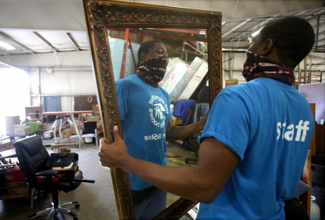 Maurice Horner of Canton carries a mirror to a customer's car at Habitat for Humanity ReStore. Horner got the job at ReStore with the help of Strengthening Stark's Career Connect program and a career navigator at the Greater Stark County Urban League. (IndeOnline.com / Kevin Whitlock)