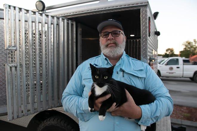 Berkley Hill, animal cruelty investigator in Pamlico County, holds Oreo who has found himself 500 miles from home. [Bill Hand / Sun Journal Staff]