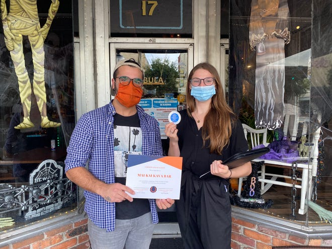 Rochelle Crevier, right, presents a certificate of safety and sticker to Clayton French of Mai Kai Kava Bar, 17 W. University Ave., after the restaurant passed the group COVID Conscious Gainesville's inspection for COVID-19 protocols.