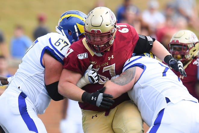 Elon defensive lineman Tristen Cox, middle, plows through Delaware offensive linemen Connor Lutz, left, and Mario Farinella, right, during the Phoenix's blowout victory in a CAA game last October.
