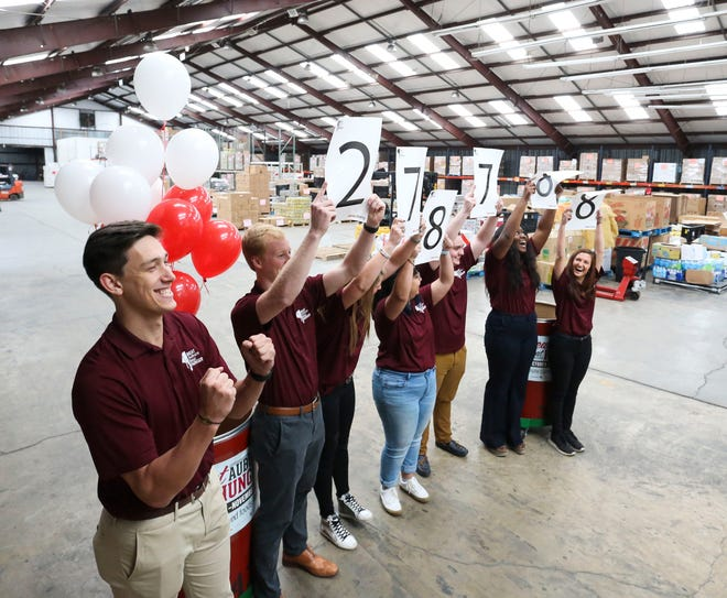 University of Alabama students hold up the total number of pounds collected for the Alabama side in the Beat Auburn Beat Hunger food drive at the West Alabama Food Bank Friday, Nov. 22, 2019. Alabama won the annual competition, collecting 278,888 pounds of food. Between the two schools, 508,149 pounds of food was collected. [Staff Photo/Gary Cosby Jr.]
