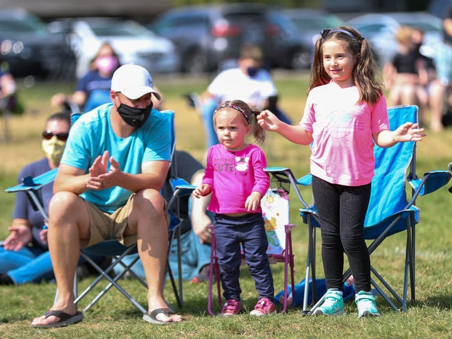 "Ron Dimmerling and his daughters, Rosa, 2, and Annie, 5, watch the marching band perform its ""parking lot concert"" Sept. 26."
