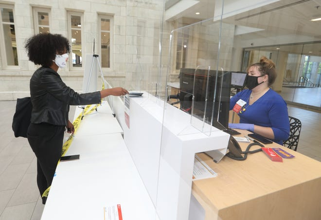 Kiera Chatman of Columbus gets a replacement library card from Elena Ende, a customer service specialist, on Sept. 29 at the Main Branch of the Columbus Metropolitan Library system. All 23 branches have reopened after being closed because of the COVID-19 coronavirus pandemic.