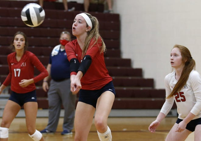 Hartley's Colleen Sweeney (center) hits a return during a match against Watterson on Sept. 10 as Katie Heuser (17) and Lauren Johnson look on. The three helped the Hawks win 11 of their first 13 matches this season.
