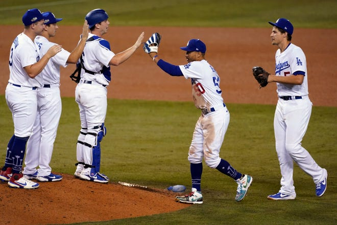 The Los Angeles Dodgers celebrate a 4-2 win over the Milwaukee Brewers in Game 1 of a National League wild-card baseball series Wednesday, Sept. 30, 2020, in Los Angeles.