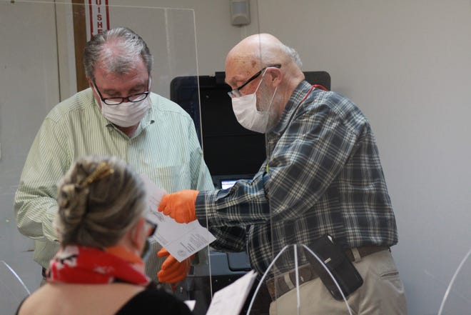 Jerry Wallin (left) and Dyatt Smathers (right) review mail in ballots  during a Sept. 29 meeting of the Madison County Board of Elections.