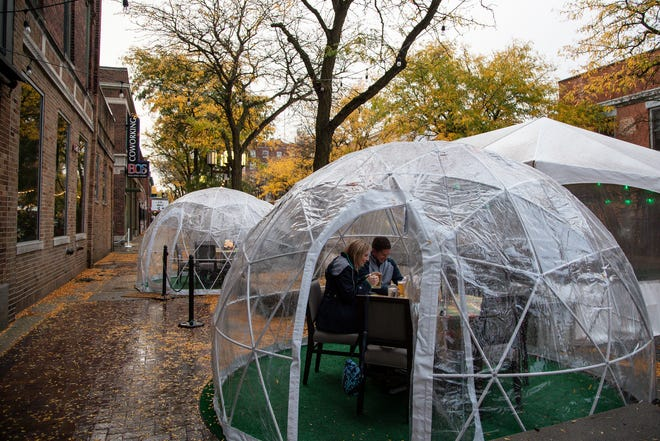 Melanie Deisler and her husband Rick both of Ypsilanti Township get ready to order food to celebrate their 20th anniversary inside of an igloo outside of Bobcat Bonnie's in downtown Ypsilanti, Wednesday, Sept. 30, 2020.