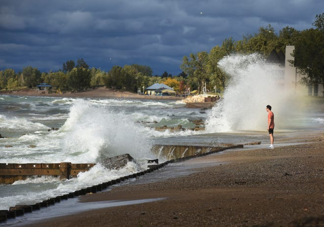 A man looks out over Lake Michigan as waves crash near Lions Park Beach in St. Joseph, Mich., Wednesday, Sept, 30, 2020.