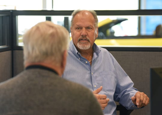 Walt Tutak, right, of Matthews Hargreaves Chevrolet, talks with customer Brian Scraggs. Tutak began to see an inventory crunch ease in September, and expects the dealership to sell more vehicles than it did a year ago, despite the pandemic.