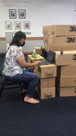Port Tariff Supervisor Jennifer N. Leon Guerrero works on top of boxes inside the Board of Directors Conference Room on Oct. 1 as her regular office area was being fumigated and deep cleaned due to exposure to the COVID-19 virus.